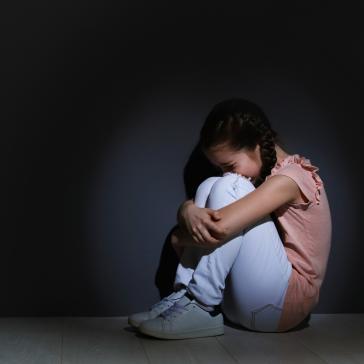 Bild eines zusammengekauerten Kindes in einem dunklen Raum