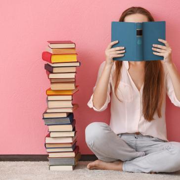 Bild einer lesenden jungen Frau, die im Schneidersitz auf dem Boden sitzt. Neben ihr steht ein Stapel Bücher