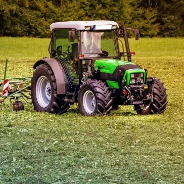 Traktor auf Wiese beim Mähen