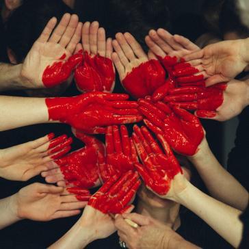 Viele Hände, die zusammengehalten werden und auf die ein großes Herz gemalt ist