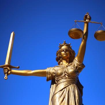 Abbildung von Justizia als goldene Statue mit verbundenen Augen, Waage und Schwert